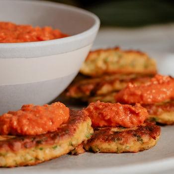 Des beignets au chou-fleur garni de sauce romesco et servis dans une assiette.