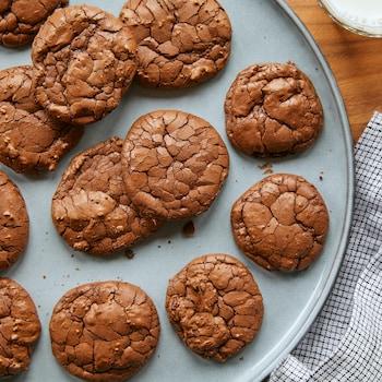Biscuits brownies dans une grande assiette de service sur une table en bois avec un linge de table et un verre de lait.