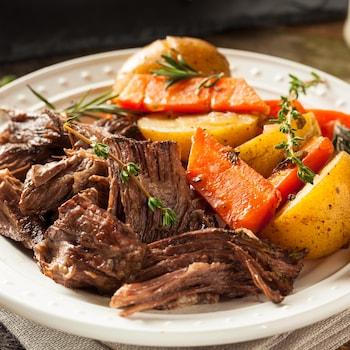 Une assiette de bœuf braisé, de pommes de terre et de carottes.