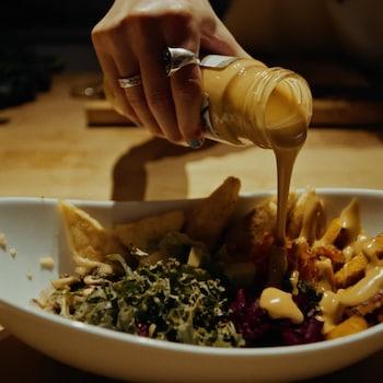 Une personne verse une vinaigrette  dans un bol.