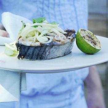 Une darne épaisse de poisson accompagnée d'un demi citron vert grillé et recouverte d'une salade de mangue verte en julienne.