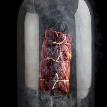 Une pièce de bœuf sous une cloche de verre avec de la fumée.