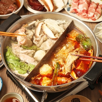 Des légumes et de la viande en train de cuire dans du bouillon à fondue chinoise.