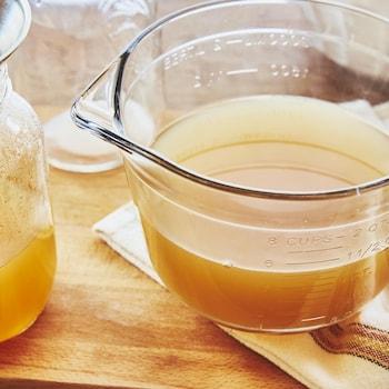 Bouillon de légumes dans une grosse tasse à mesurer posée sur un linge à vaisselle.