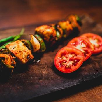 Une brochette de viande sur une planche en bois avec des morceaux de tomate.