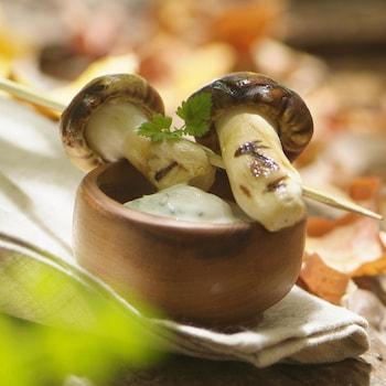 De la crème sure dans un petit bol en terre cuite et une brochette en bois de deux champignons entiers et rôtis disposée sur le dessus.