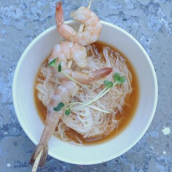 Un bol blanc de bouillon et vermicelles de riz avec une brochette de crevettes crues déposée sur le dessus.