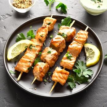Trois brochettes de saumon dans une assiette noire.