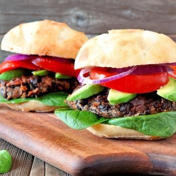 Deux burgers aux fèves noires sur une planche en bois.