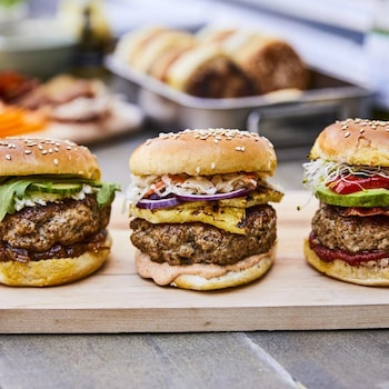 Trois burgers de porc garnis de légumes sur une planche en bois.