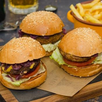 Trois burgers sur une planche en bois avec un bol de frites en arrière-plan.