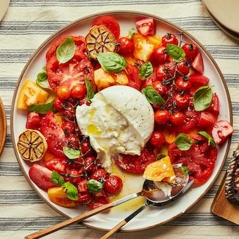 Sur une table de cuisine, est déposé une grande assiette blanche contenant des tomates ancestrales tranchées, des tomates cerises et des feuilles de basilic. Au centre est déposé une boule de fromage burrata et il y a des tranches de pain crouté à la droite de l'assiette.