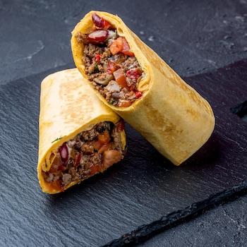 Un burrito coupé en deux sur une planche de service.