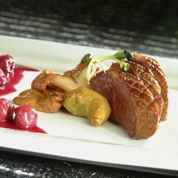 Trois tranches épaisses de canard Montmorency disposés dans une assiette blanche rectangulaire accompagnées de crosnes, de salsifis et de sauce rouge aux griottes.