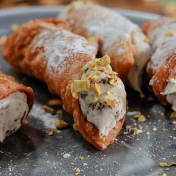 Des cannolis farcis à la ricotta et aux pistaches, servis dans une assiette.