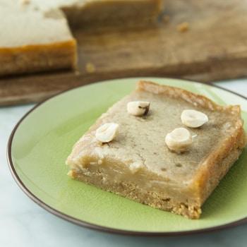 Un carré à l'érable et aux noisettes servi dans une petite assiette à dessert.