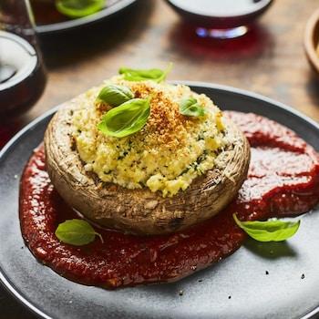 Un champignon portobello farci et gratiné, disposé sur une sauce tomate dans une assiette.