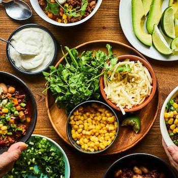 Des bols remplis de chili disposés à côté de maïs en grains, de fromage râpé, de coriandre, de yogourt et de lime.