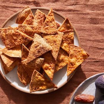 Sur une nappe, il est possible de voir une assiette contenant des chips de tortillas sucrée.