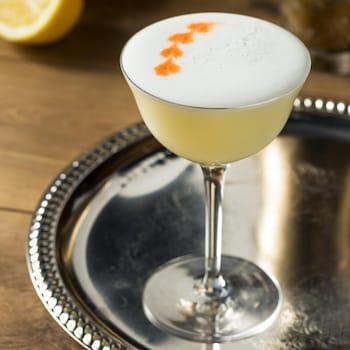 Un cocktail jaune et mousseux dans un verre sur pied présenté sur un plateau d'argent.