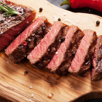 Un filet de bœuf coupé en morceaux sur une planche à découper.