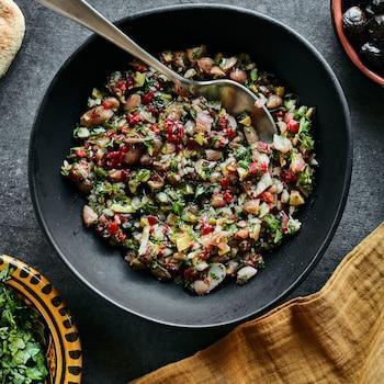 Il y a, au centre de la photo, un bol contenant le concassé de haricots à la marocaine. À gauche, au bas de la photo, il y a un bol d'herbes et en haut à droite, un bol d'olives noires.