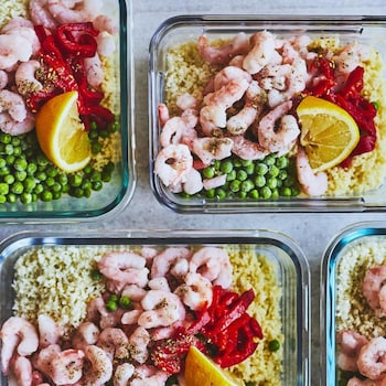 Des couscous aux crevettes, petit-pois, poivrons rouges et citron disposés dans des plats transparents.
