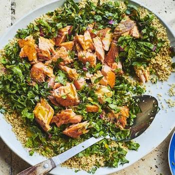 Un couscous aux feuillages et au saumon grillé disposé dans une grande assiette avec une cuillère.