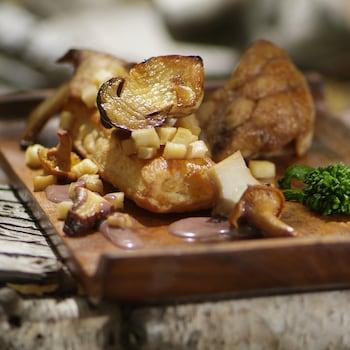 Ris de veau cuits décorés de champignons sauvages rôtis dans une assiette en bois.