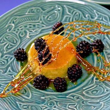 Une crème caramel recouverte de mûres dans une assiette.