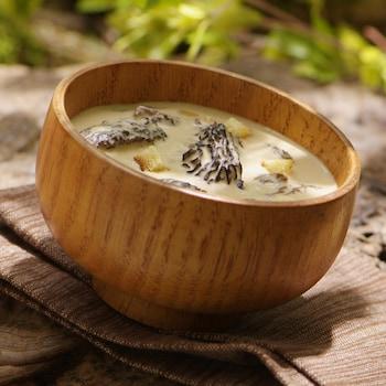 Une crème de morilles entières dans un bol en bois.