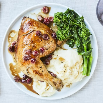 Une cuisse de poulet avec des canneberges, de la purée de pommes de terre et des légumes verts dans une assiette blanche.