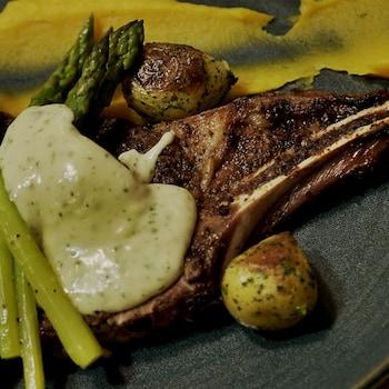 Un morceau d'entrecôte de bison recouvert de sauce et de légumes.