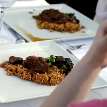 Des morceaux de viande déposés sur du riz et des légumes.