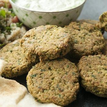 Des falafels servis avec des pains pita, du taboulé et de la sauce au tahini verte.