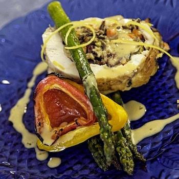 Un morceau de viande rempli de farce avec des légumes dans une assiette.