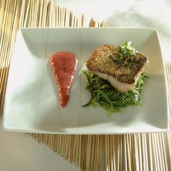 Un filet de doré déposé sur un nid de salicornes et une traînée de jus de fraise à l'oseille juste à côté.