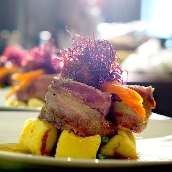 Une assiette de filet de porc lardé avec des gnocchis de pommes de terre.