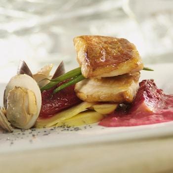 Un filet de sébaste dans une assiette accompagné de légumes et d'une purée de figues rose.