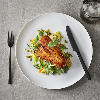 Un filet de truite déposé sur une salade dans une assiette.