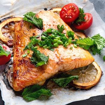 Un morceau de saumon avec des citrons, des tomates et des oignons verts sur du papier parchemin.