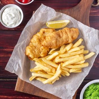 Un fish and chips servi sur une planche avec trois sauces différentes.