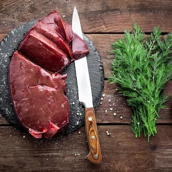 Un foie de veau en morceau sur une planche avec un couteau et  un bouquet d'aneth.