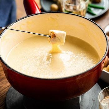 Une fourchette à fondue avec un pain au bout qui vient d'être trempé dans le fromage.