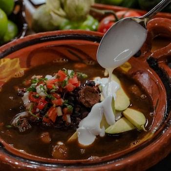 Une cocotte de frijoles charros avec une garniture de tomates et d'oignons en dés (pico de gallo)