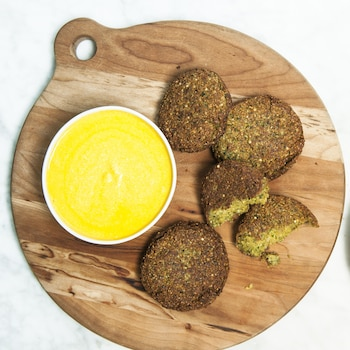 Des galettes de falafel servies sur une planche de bois, accompagnées d'une sauce au piment jaune et d'une gamme d'épices péruviennes.