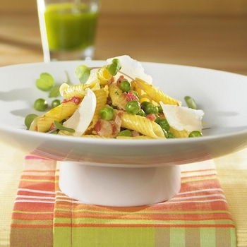 Garganellis aux bajoues de porc séchées aux pois verts et aux tomates dans une assiette.