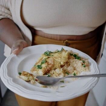 Une assiette contenant du gari (semoule) et une omelette, parsemée d'herbes fraîches.