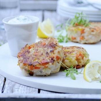 Deux petits gâteaux d'aiglefin et crevettes avec des morceaux de citron et un petit pot de crème sure.