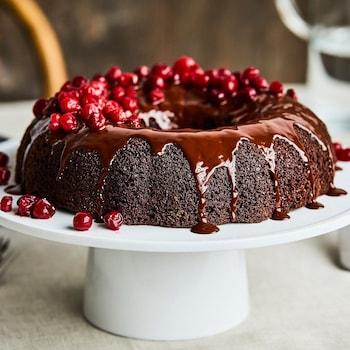 Un gâteau au chocolat et aux canneberges sur un présentoir à gâteau blanc sur pied.
